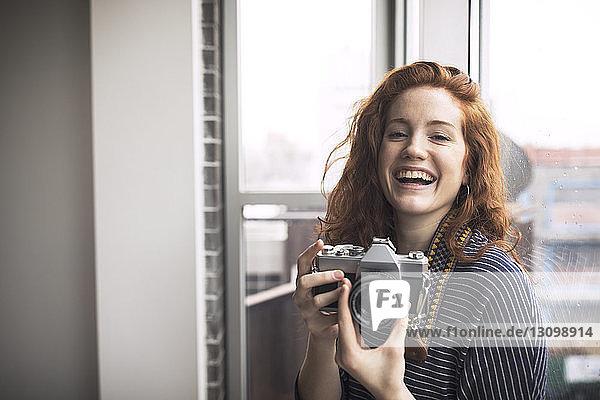 Portrait of happy woman holding camera