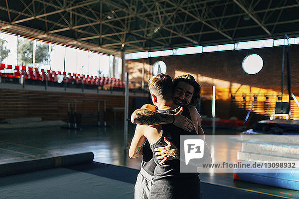 Glückliche Freunde umarmen sich im Stehen im Fitnessstudio