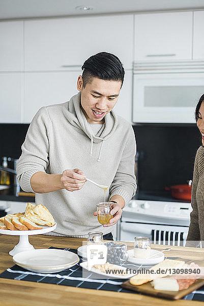 Man with girlfriend preparing breakfast in kitchen
