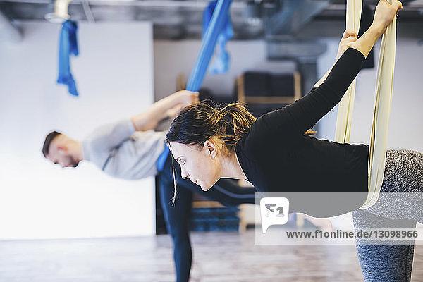 Freunde benutzen Hängematten  während sie Anti-Schwerkraft-Yoga im Fitnessstudio praktizieren