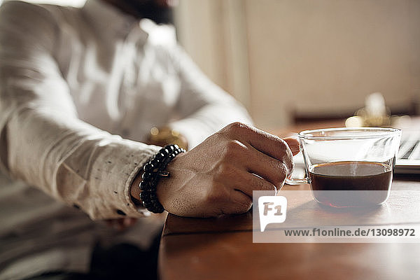 Ein Mann hält eine schwarze Kaffeetasse am Tisch