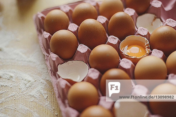 High angle view of eggs in carton on wooden table in kitchen