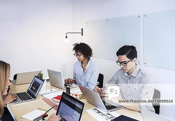 Hochwinkelansicht von Geschäftsleuten mit Laptop-Computern im Sitzungssaal