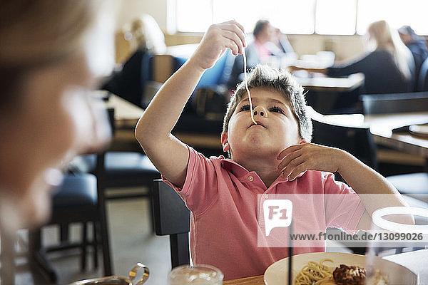 Süßer Junge isst Nudeln am Restauranttisch