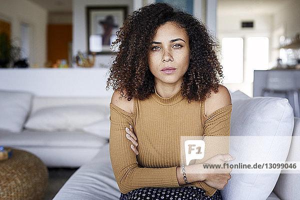 Porträt einer selbstbewussten Frau mit verschränkten Armen  die zu Hause auf dem Sofa sitzt
