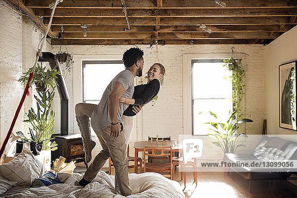 Fröhliches multiethnisches Paar tanzt zu Hause auf dem Bett