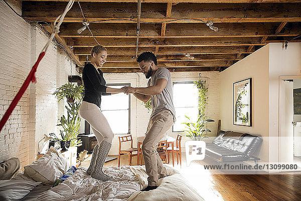 Seitenansicht eines glücklichen Paares  das zu Hause auf dem Bett tanzt