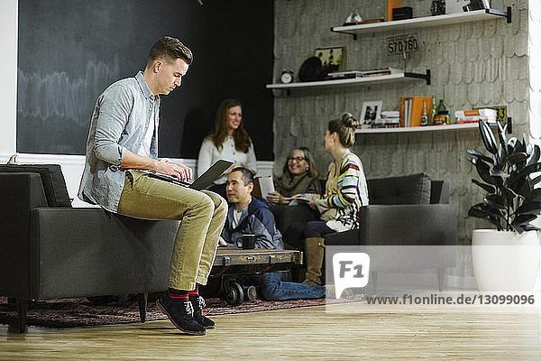 Geschäftsmann benutzt Laptop-Computer  während sich Kollegen im Hintergrund im Büro unterhalten