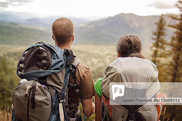 Rückansicht eines Paares mit Rucksäcken beim Blick auf Berge