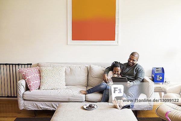 Glücklicher Vater und Tochter schauen auf Tablet-Computer  während sie auf dem Sofa sitzen