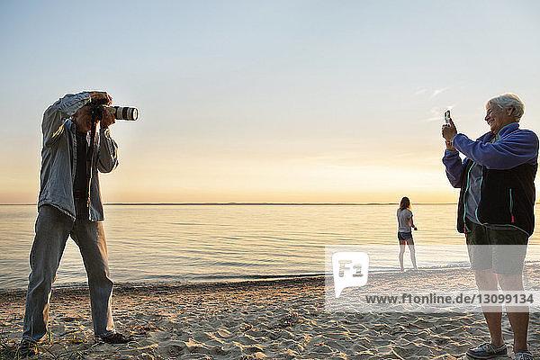 Älterer Mann fotografiert Frau am Strand bei Sonnenuntergang