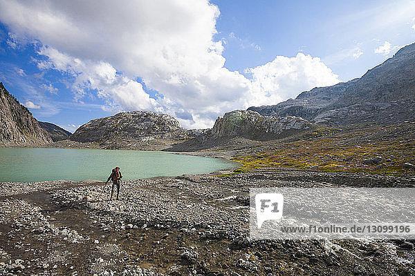 Full length of hiker standing on lakeshore at Garibaldi Provincial Park against sky