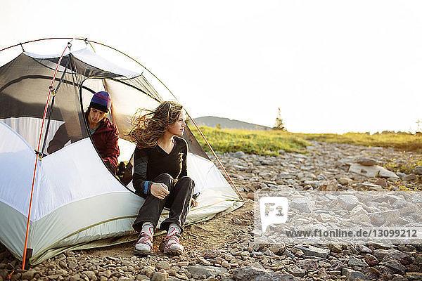 Glückliches Paar entspannt sich im Zelt bei klarem Himmel