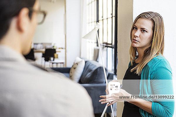 Geschäftsfrau im Gespräch mit männlichem Amtskollegen