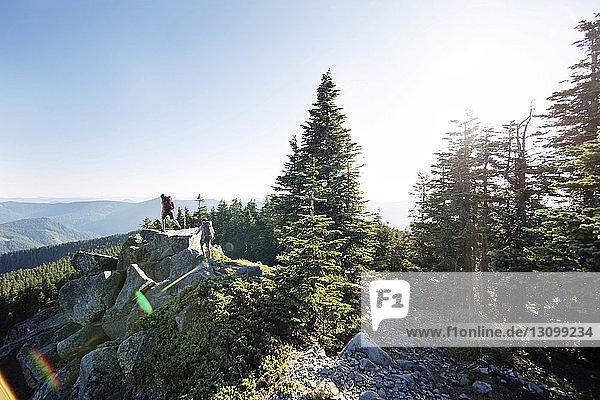 Hochwinkelansicht eines auf dem Berg wandernden Paares bei klarem Himmel
