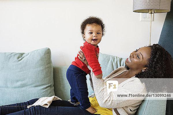 Verspielte Mutter schaut dem Sohn beim Entspannen auf dem Sofa zu