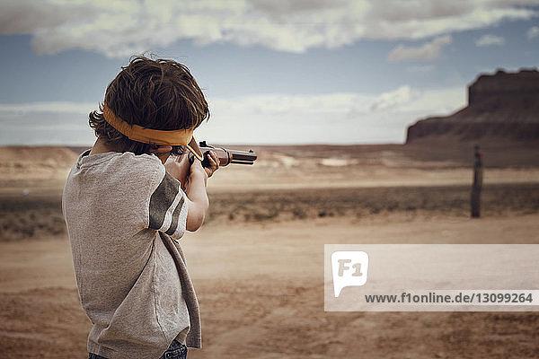 Junge zielt Gewehr  während er auf dem Feld gegen den Himmel steht