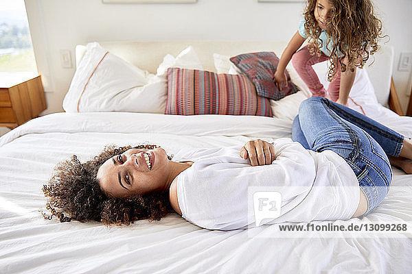 Porträt einer glücklichen Mutter  die mit ihrer Tochter spielt  während sie zu Hause im Bett liegt