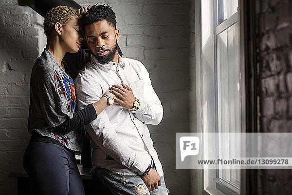 Entspanntes junges Paar mit geschlossenen Augen steht zu Hause am Fenster