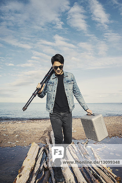 Full length of young man with briefcase and tripod walking on logs at beach