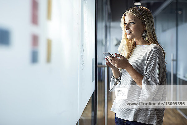 Thoughtful smiling businesswoman holding mobile phone while standing at corridor