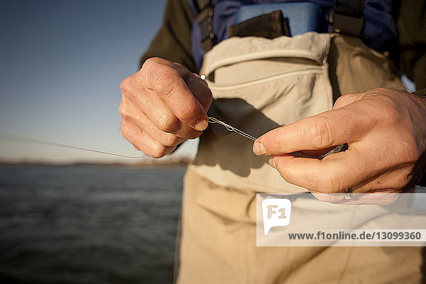 Midsection of man holding fishing line at beach