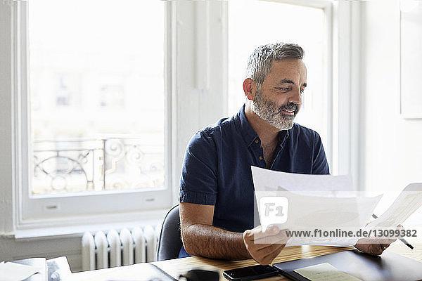 Geschäftsmann prüft Dokumente  während er im Büro am Schreibtisch sitzt