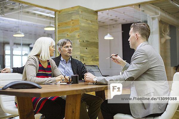 Geschäftsmann erklärt den Kollegen am Schreibtisch im Büro