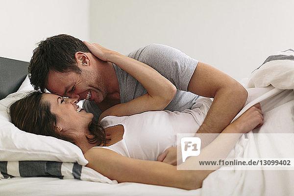 Nahaufnahme eines lächelnden Paares im Bett zu Hause