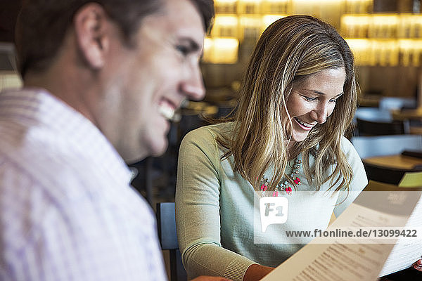 Cheerful mid adult couple reading menu in restaurant