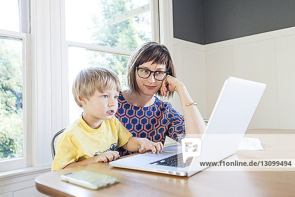 Mother looking at son using laptop computer on table at home