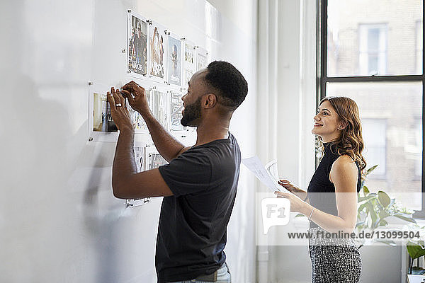 Geschäftsmann hängt Fotoausdrucke am Schwarzen Brett an  während eine lächelnde Kollegin ihm im Büro zur Seite steht