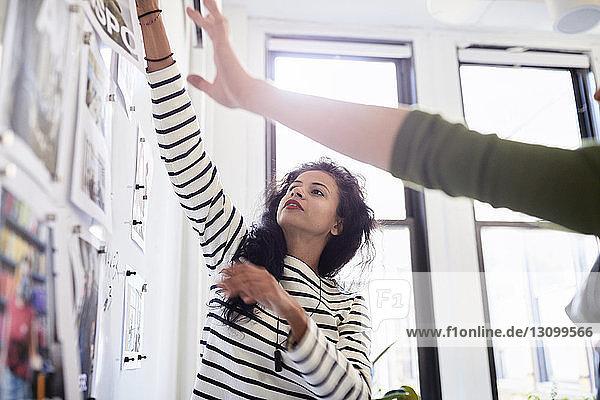 Niedrigwinkelansicht von Geschäftsfrauen  die über Fotoausdrucke am Schwarzen Brett im Büro diskutieren