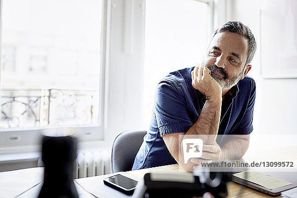 Thoughtful businessman with hand on chin sitting at desk in creative office