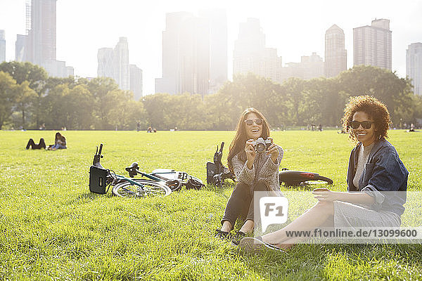Happy woman holding camera while relaxing with friend on grassy field