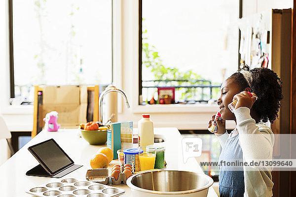 Mädchen sieht Rezept im Tablet-Computer  während sie in der Küche Cupcakes backt