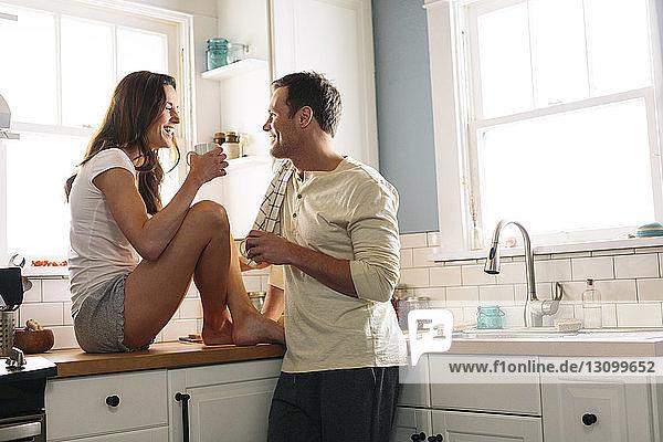 Glückliches Paar trinkt zu Hause Kaffee in der Küche