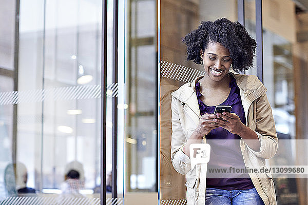 Happy businesswoman using smart phone while standing at doorway in office