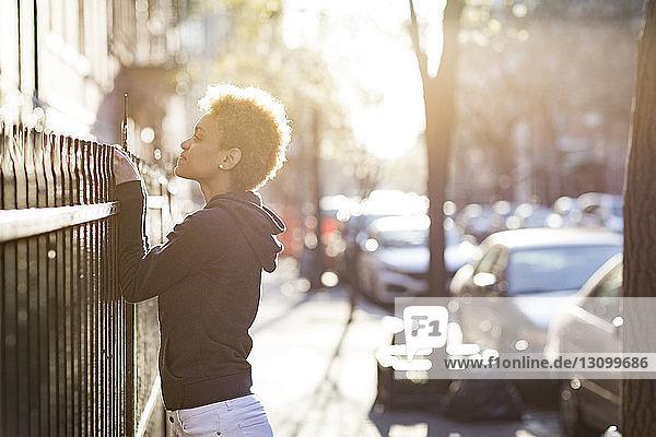 Junge Frau  die über das Geländer schaut  während sie auf dem Bürgersteig steht