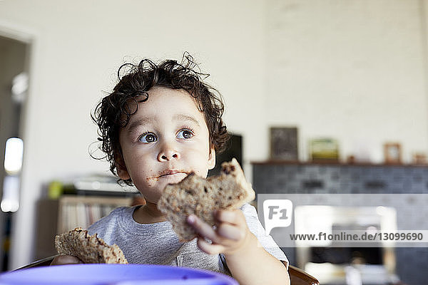 Close-up of cute thoughtful baby boy holding breads while looking away at home