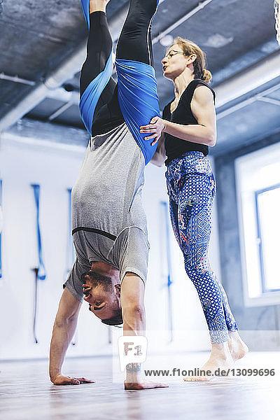 Yogalehrerin hilft einem Mann  der in der Hängematte hängt  während er im Fitnessstudio trainiert