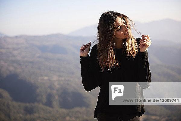 Frau spielt mit Haaren  während sie gegen Berge steht