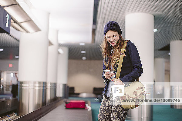 Happy woman using mobile phone while standing by baggage claim at airport