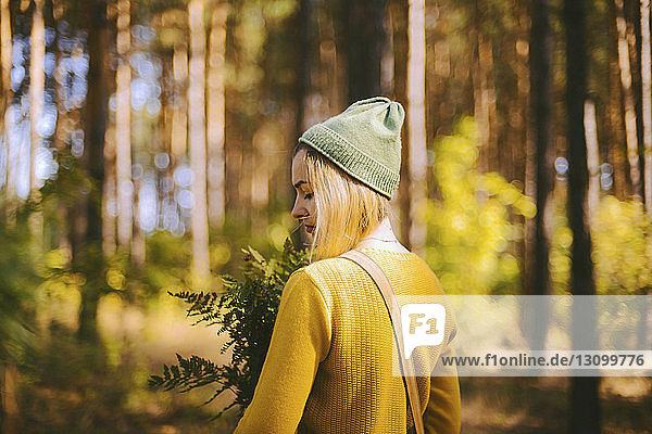 Rückansicht einer Frau  die eine Pflanze hält  während sie im Wald steht