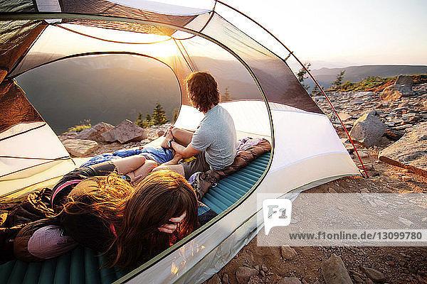Ehepaar entspannt sich im Zelt auf dem Berg