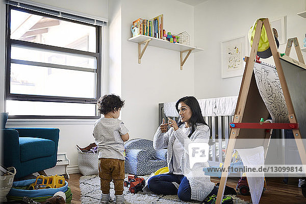 Mother teaching sign language to son at home