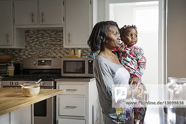 Thoughtful woman carrying daughter in kitchen