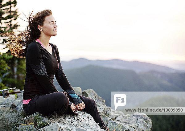 Frau meditiert  während sie auf einer Felsformation vor klarem Himmel sitzt