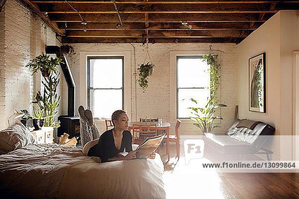 Frau liest Zeitung  während sie zu Hause im Bett liegt