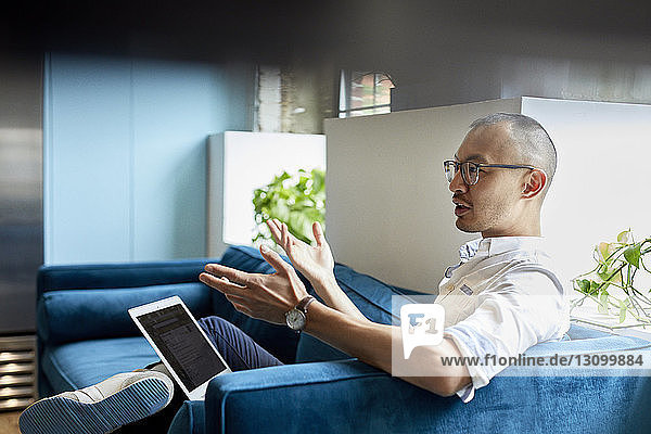Businessman with laptop gesturing while sitting on sofa at creative office